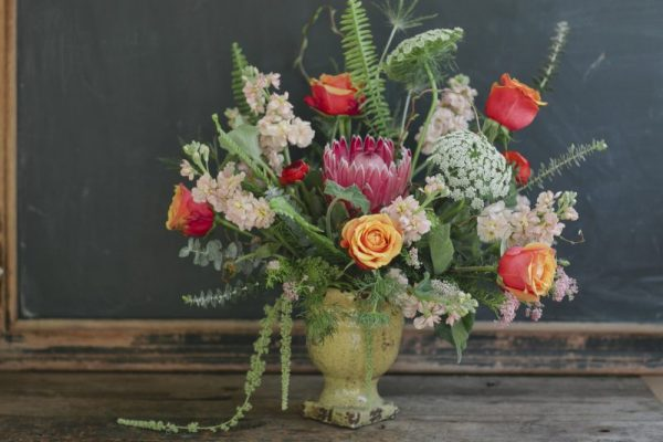 Extra Large arrangement in a custom porcelain vase containing proteas, roses, stock, chocolate lace, and sword fern
