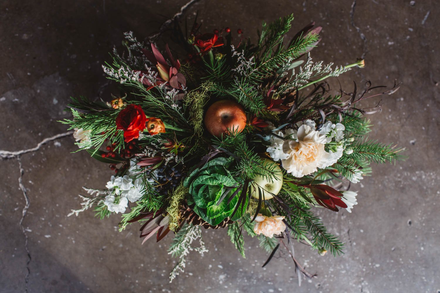 christmas centerpieces with pine, cedar, cabbage, red berries, and bay leaves