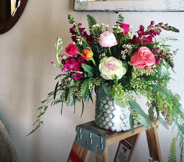 flower arrangement in medium-sized custom vase with roses, stock, seeded eucalyptus and sword fern in a custom vase