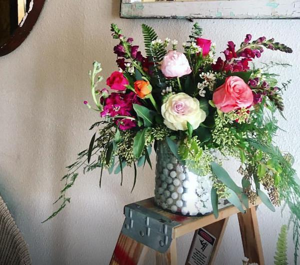 flower arrangement in medium-sized custom vase with roses, stock, seeded eucalyptus and sword fern in a custom vase