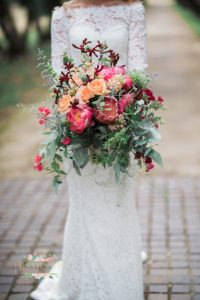 Bridal Bouquet: Bride holding huge bouquet filled with roses, proteas, peonies, kangaroos paw