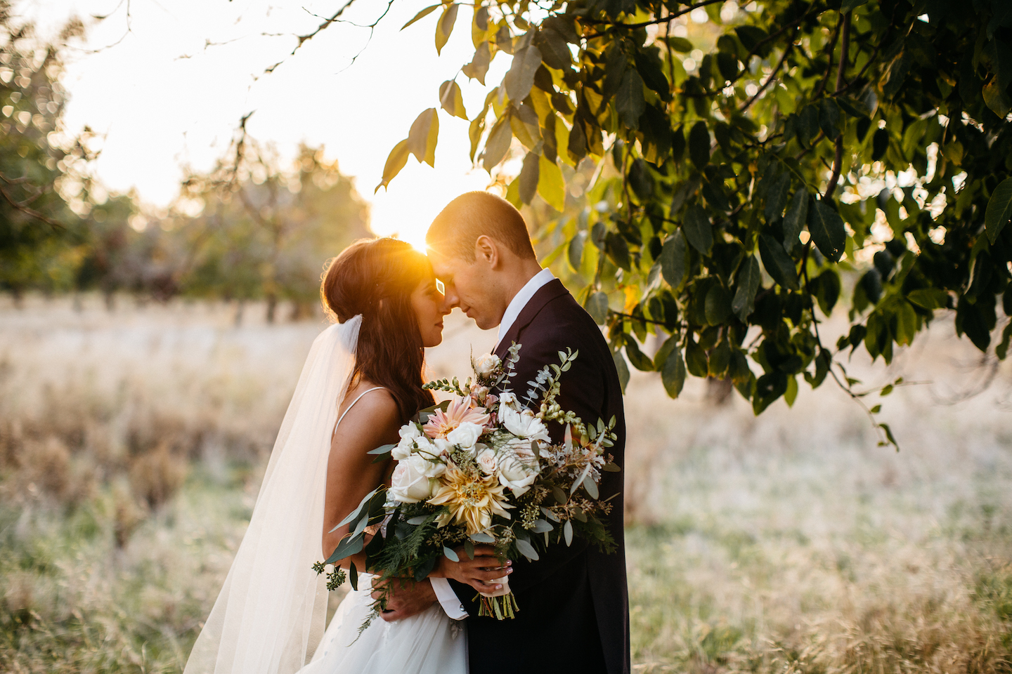 bride and groom in a field at sunset holding a bridal bouquet of dahlias, roses eucylyptus
