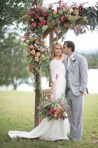 bride and groom standing under flower arch